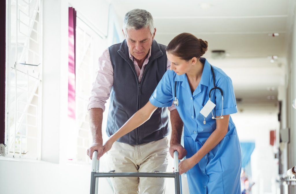 Nurse helping senior man with walking aid in senior community.