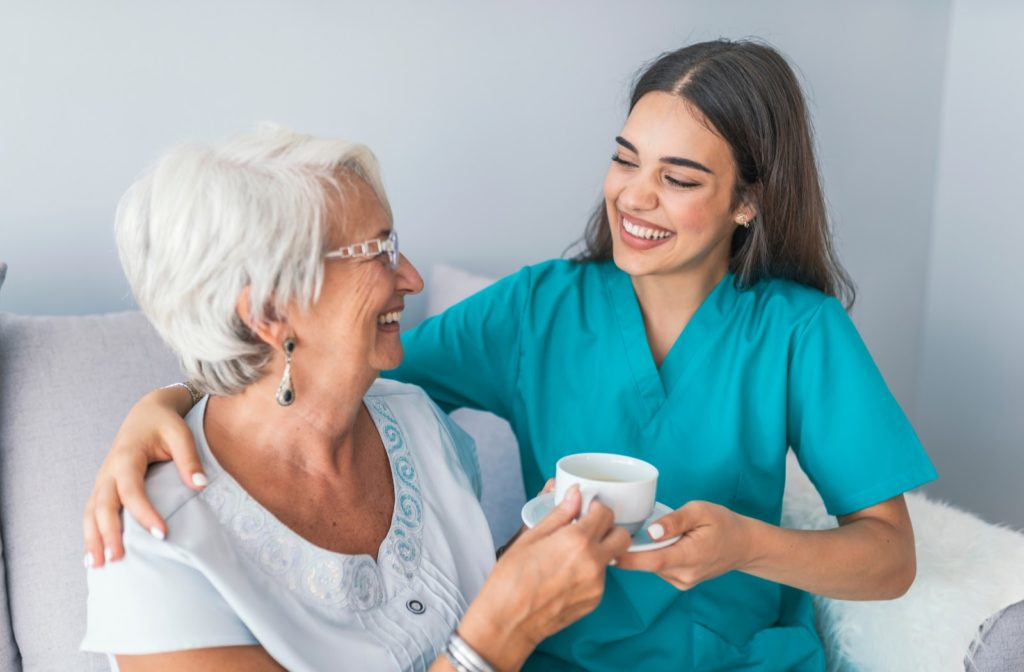 Happy senior woman with happy caregiver while passing cup of tea to each other.